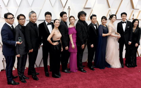 The cast and crew of the Korean film Parasite pose for a photo on the Oscars red carpet. The film made history at the 2020 awards show as the first international film to win the Best Picture category. Photo courtesy of Kevin Mazur/Getty Images.
