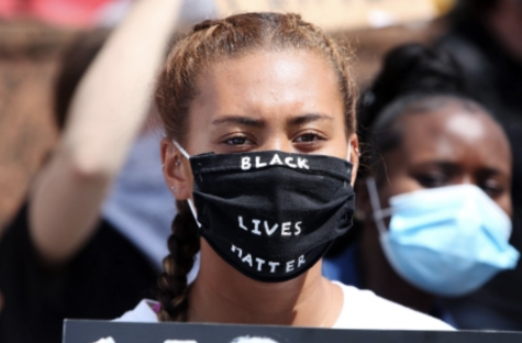 A young woman attends a Black Lives Matter protest on Blackout Tuesday. The movement was initiated by two African-American women in the music industry with the intention of promoting African-American music and movies. Photo courtesy of David Buchan/Shutterstock.